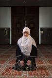 Young muslim pray in mosque. Muslim girl in mosque in tradicional islam clothes pray and reading Koran Stock Images