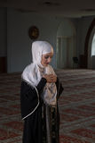 Young muslim pray in mosque. Muslim girl in mosque in tradicional islam clothes pray and reading Koran Stock Photo