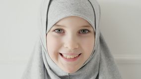 Young muslim teen girl in hijab shyly looking at camera and smiling. stock video