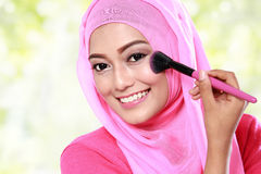 Young muslim woman applying blush on Royalty Free Stock Images
