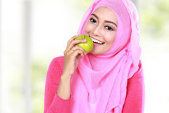 Young muslim woman bite an apple Stock Image