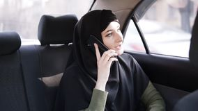 Young muslim woman in black hijab sitting in car on passenger rear seat and talking on cell phone, looking at window. Lens flares on her face stock footage