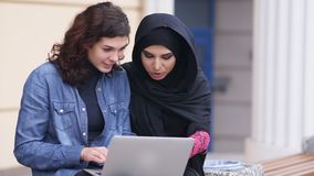 Young muslim woman in black hijab is talking to her female caucasian friend. Two attractive young women sitting outside. And using laptop. Cross-cultural stock footage
