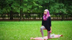 Young muslim woman in burqa crouching with dumbbells in summer park stock footage