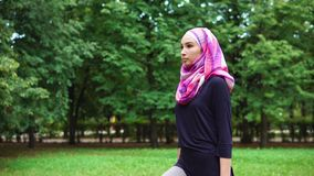 Young muslim woman in burqa crouching with dumbbells in summer park stock video