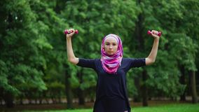 Young muslim woman in a burqa doing exercises with dumbbells in a summer park stock footage
