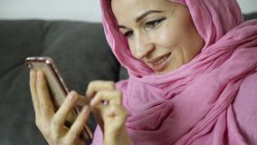 Young Muslim woman is chatting with her friends. mobile phone in the hands of a arabian woman wearing a hijab.  stock video