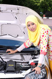 Young muslim woman checking engine royalty free stock photography