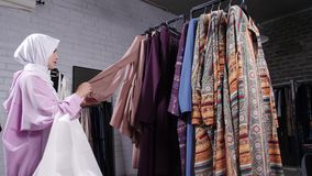 A young Muslim woman choosing clothes at the store stock footage