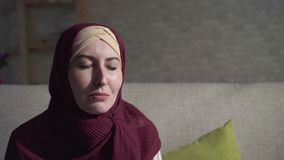 Young muslim woman in depression crying sitting on the couch in the living room close up. Young muslim woman in a traditional scarf in depression crying sitting stock footage
