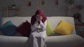 Young muslim woman in depression crying sitting on the couch in the living room. Young muslim woman in a traditional scarf in depression crying sitting on the stock video