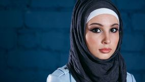 A young Muslim woman dressed in hijab looks straight into the camera stock footage