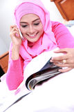 Young muslim woman enjoy reading a magazine while talking on the Royalty Free Stock Image