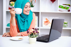 Young muslim woman enjoying morning day with a cup of tea and mo Stock Images