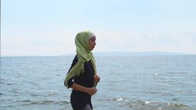 A young Muslim woman goes in for sports near the ocean or the sea, on summer day. A young Muslim woman in a veil, which closes her hair, goes in for sports near stock footage