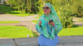 A young Muslim woman in a green scarf and sunglasses in the park drinks coffee and is in the messenger. The average plan stock video footage