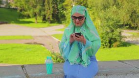 A young Muslim woman in a green scarf and sunglasses in the park drinks coffee and is in the messenger. The average plan stock footage