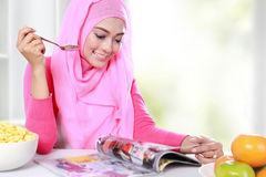 Young muslim woman had a breakfast while reading a magazine Stock Photography