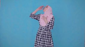 A young Muslim woman having an asthma attack,uses spray. Portrait young Muslim woman having an asthma attack,uses spray blue isolate background stock footage