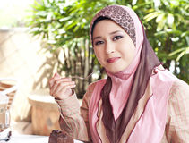 Young muslim woman having lunch. At cafeteria stock photography