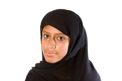 Young Muslim Woman (headshot). A young Muslim woman wearing a black head scarf looking at the camera. Serious Stock Photo