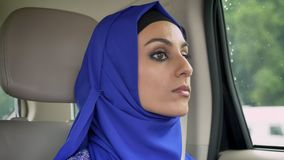 Young muslim woman in hijab in car on passenger rear seat looking forward, serious.  stock footage
