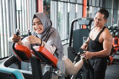 Young muslim woman hijab doing back leg presses Stock Photos