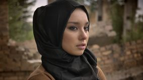Young muslim woman in hijab looking away and at camera, worried and afraid, ruined building in background.  stock video footage