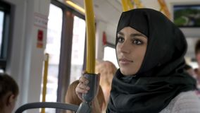 Young muslim woman in hijab is riding in bus, transport concept, urban concept, dreaming concept, side view.  stock video