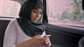 Young muslim woman in hijab is riding in car, surfing internrt on smartphone, transport concept, communication concept.  stock video