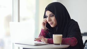 Young muslim woman in hijab sitting in cafe with cup of coffee and talking on her mobile phone while using her laptop. She is searching for something in stock footage