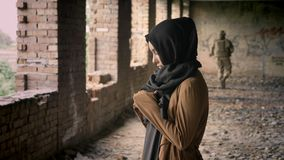 Young muslim woman in hijab standing in abandoned building, soldier walking in background, military.
