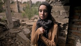 Young muslim woman in hijab standing near ruined brick building and looking at camera, sad and depressed.  stock video footage
