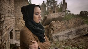 Young muslim woman in hijab standing near ruined building and looking at camera with scared and worried expression, ruin