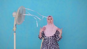 Young Muslim woman in hijab suffering from hot weather cooled by fan. Looking at camera blue isolate background stock footage