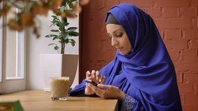 Young muslim woman in hijab typing on phone and sitting in cafe, beautiful female with pierced nose.  stock video
