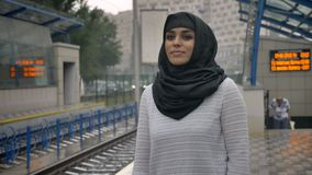 Young muslim woman in hijab is waiting for train n railway station, raining, religion concept, urban concept. weather. Concept stock footage