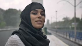 Young muslim woman in hijab is waiting for train on railway station, raining, religion concept, urban concept. weather. Concept stock video footage