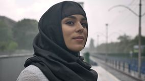 Young muslim woman in hijab is waiting for train on railway station, raining, religion concept, urban concept. weather. Concept, side view stock video footage