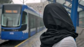 Young muslim woman in hijab is watching how train is coming, raining, religion concept, urban concept.  stock video