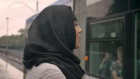 Young muslim woman in hijab is watching how train is coming under raining, religion concept, transport concept, weather. Concept stock video