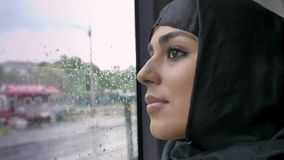 Young muslim woman in hijab is watching in rainy window in bus, transport concept, urban concept, weather concept. Dreaming concept, side view stock video
