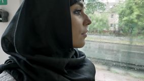 Young muslim woman in hijab is watching in window in trolleybus, rainy weather. Young muslim woman in hijab is watching in window in trolleybus, rainy weather stock video