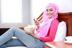 Young muslim woman holding mobilephone and a bowl of popcorn Stock Image