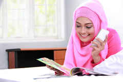 Young muslim woman holding mobilephone while reading a magazine. Portrait of young muslim woman holding mobilephone while reading a magazine on bed Stock Photography