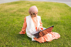 Young Muslim woman with laptop in the park Stock Images