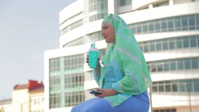 A young Muslim woman in a light scarf on the background of a modern building. The average plan stock footage