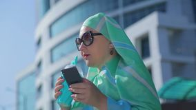 A young Muslim woman in a light scarf on the background of a modern building. The average plan stock video footage