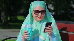A young Muslim woman in a light scarf and dark glasses sits on a bench in the park and drinks coffee and talks in the. Messenger. The average plan stock video