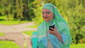 A young Muslim woman in a light scarf in the park is drinking coffee and talking in the messenger with headphones. The average plan stock footage